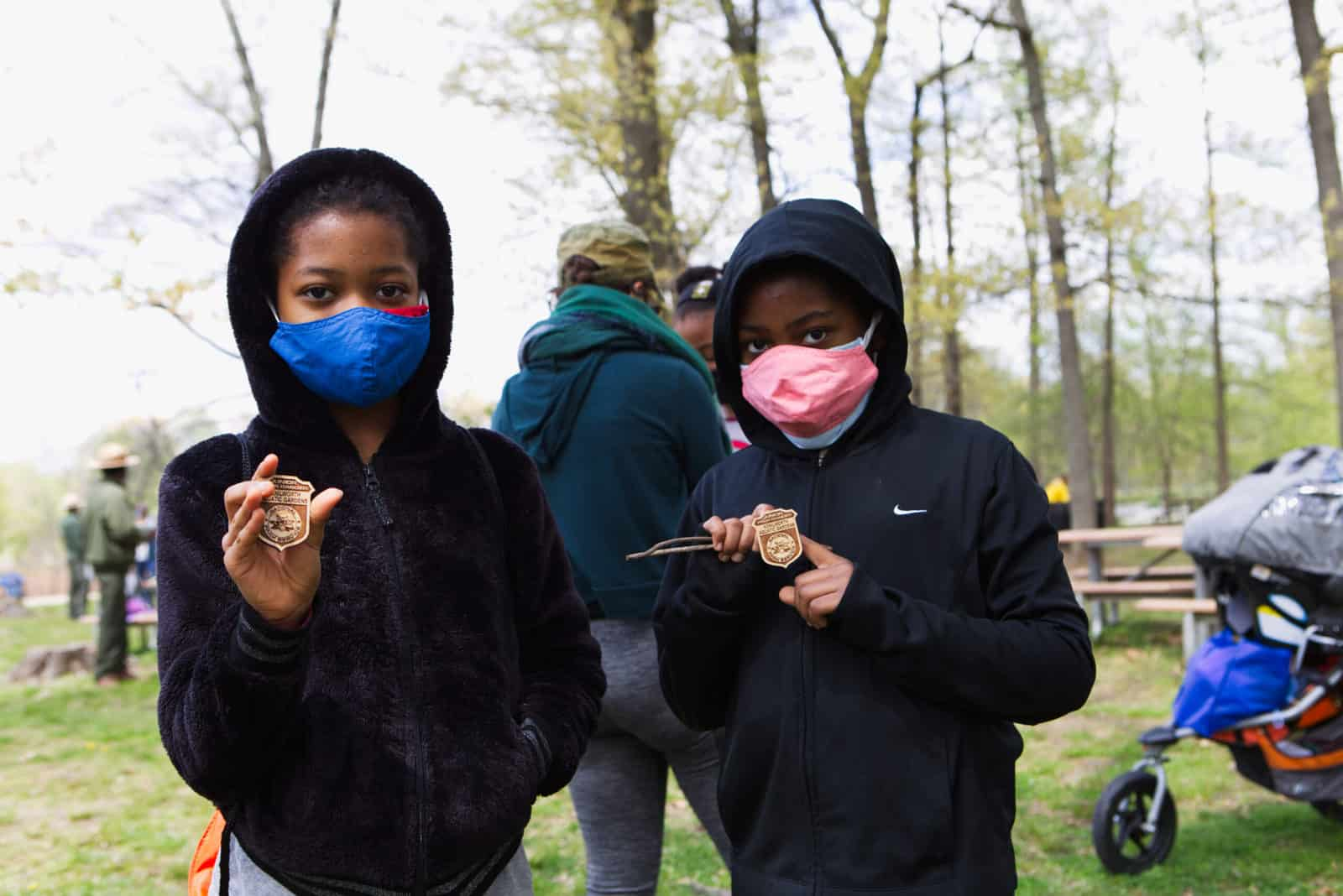 A photo of two girls holding up junior ranger badges at kenilworth aquatic gardens