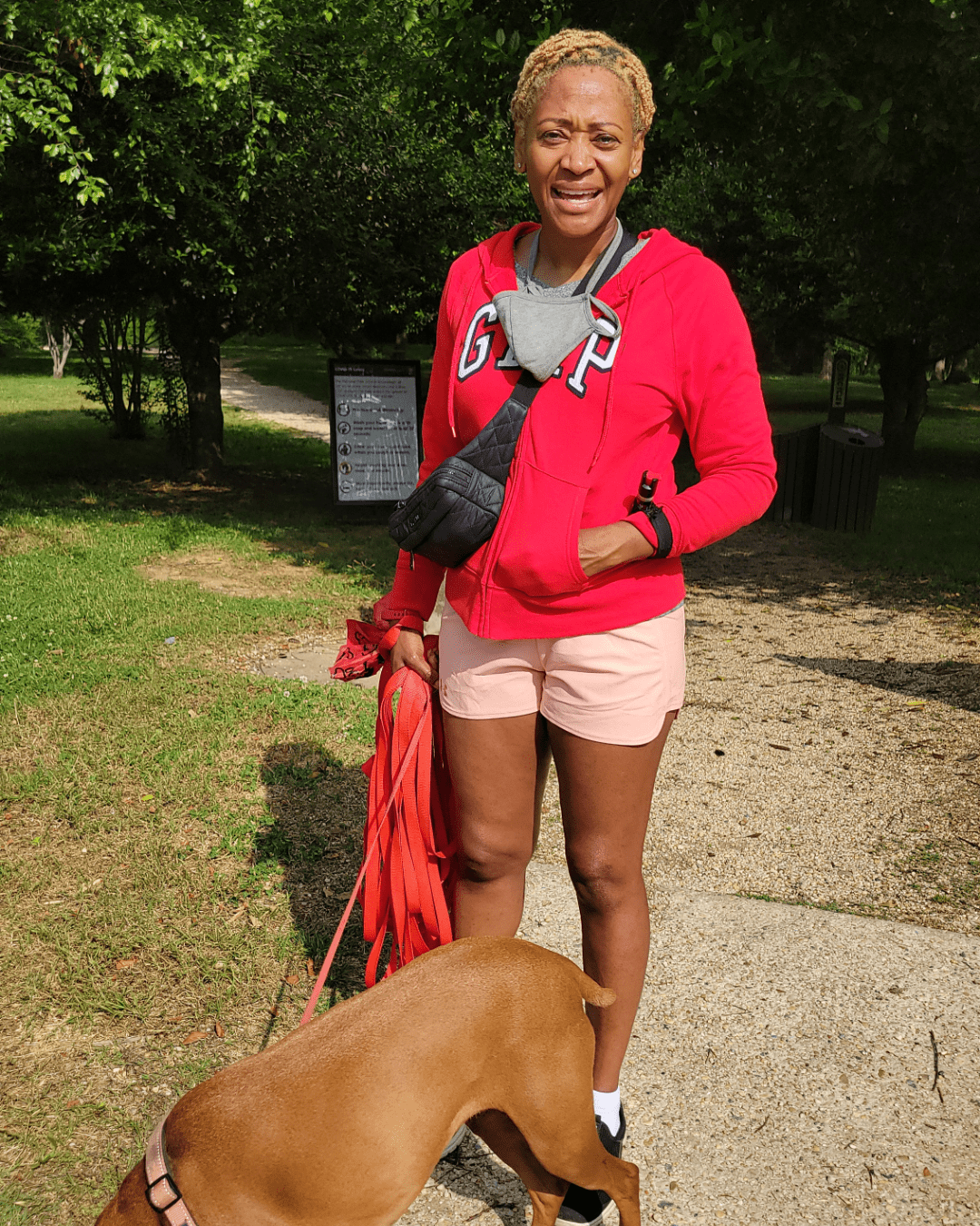 Photo of Junel Jeffrey in a red sweatshirt and shorts, smiling for the camera with her brown dog at the entrance to Kenilworth Aquatic Gardens.